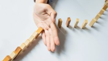 businessman-hand-stop-dominoes-continuous-toppled-or-risk-with-copyspace_1423-17